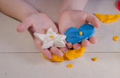 Barnhänder och plasticine Arkivfoto