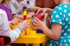Barnhänder som bygger torn ut ur trätegelstenar arkivfoto