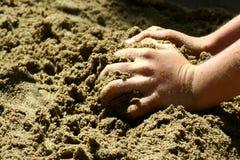 Barnhänder som griper sand på en strand Arkivfoto