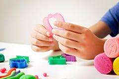 Barnhänder som spelar med att modellera lera eller plasticine på den vita tabellen Arkivbilder