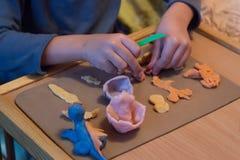 Barnhänder som spelar med färgrikt, behandla som ett barn lekdeg, plasticine arkivbilder