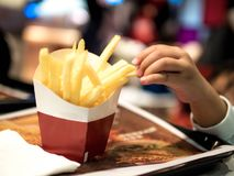 Barnhänder som väljer franska småfiskar på tabellen, pommes frites royaltyfri fotografi