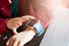 Barnhand som bär den smarta klockan Wearable grejbegrepp Pys som använder den smarta klockan, medan placera på tabellen och arbet Royaltyfri Foto