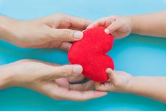Barnhand som ger röd hjärta till hennes farsa, lycklig familj arkivbild