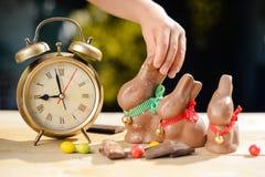 Barnhand som tar den stora chokladkaninen bredvid retro Royaltyfri Foto