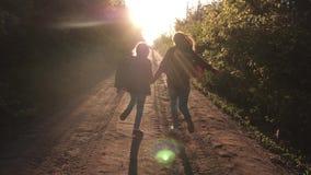 Barnhandelsresande Fotvandrareflicka lyckliga flickahandelsresande med ryggsäckar som körs längs landsvägen som rymmer händer i s lager videofilmer