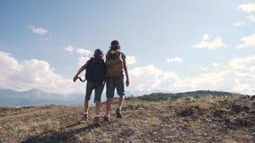 Barnhandelsresande två små flickor med ryggsäckar går på en vandring och rymmer händer Turism med barn arkivfilmer
