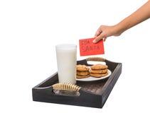 Barnhanderbjudanden mjölkar och kakor för jultomten II Arkivfoto
