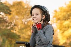 Barnhjälm som rider en cykel Flickan i parkerar att rida en cykel arkivbilder