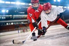 Barnhockeyspelare som behandlar pucken på is royaltyfri foto