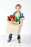 Barnholdingkartongen packade med toys royaltyfri foto