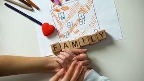Barninnehavhanden av den vuxna personen, familjord gjorde från kuber på husbild arkivfilmer