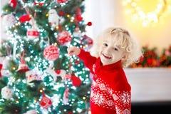 barnjul som dekorerar treen Unge på Xmas-helgdagsafton arkivfoton