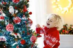 barnjul som dekorerar treen Unge på Xmas-helgdagsafton royaltyfri foto