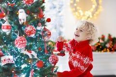 barnjul som dekorerar treen Unge på Xmas-helgdagsafton royaltyfri fotografi