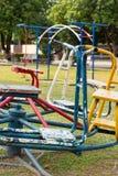 Barnkarusell och utrustning i lekplats Fotografering för Bildbyråer