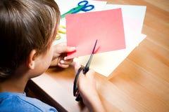 Barnklipp färgade papper med sax på tabellen Arkivfoton