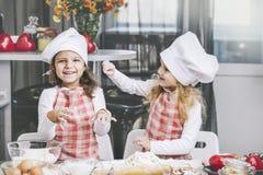 Barnkock för två lycklig små flickor med mjöl och deg på taen royaltyfri fotografi