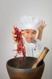 Barnkockar eller kockbarnet lagar mat Arkivfoto