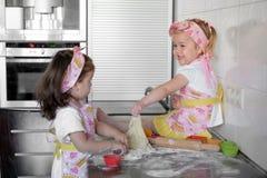 Barnkocken för två är den lyckliga små flickor med mjöl och deg på tabellen i köket älskvärd och härlig royaltyfria foton