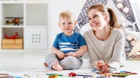 Barnkreativitet fostra och behandla som ett barn sonen som tillsammans drar arkivbild