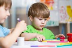 Barnkreativitet Ungar som hugger från lera Gulliga pyser gjuter från plasticine på tabellen i barnkammarerum arkivfoto