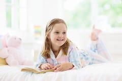 Barnläsebok i säng Ungar läste in sovrummet royaltyfri foto