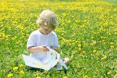Barnläsning i fält av maskrosor Royaltyfri Fotografi