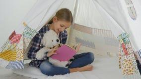 Barnläsning som studerar i lekrum, unge som spelar på lekplatsen som lär flickan arkivbild