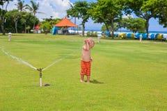 Barnlek, bad och färgstänk under vattenspridaresprej arkivfoton