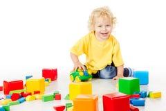 Barnlek blockerar leksaker, att spela för unge som isoleras på vit Arkivfoton
