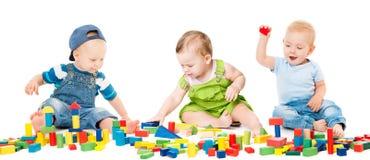 Barnlek blockerar leksaker, ungegruppen som spelar färgrika tegelstenar Arkivbild