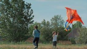 Barnlek för den bakre sikten med en drake, lite flicka och en pojke lät en flygaorm i ängen Lyckligt och bekymmersl?st stock video