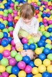 Barnlek i färgrika bollar Arkivbild