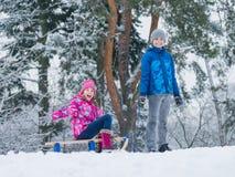 Barnlek i snö med släden Royaltyfri Bild