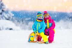 Barnlek i snö på släde i vinter parkerar Royaltyfri Bild