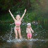 Barnlek i vattnet i den varma sommaren flickor har gyckel som plaskar i floden royaltyfri bild