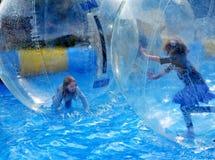 Barnlek inom av genomskinliga plast- bollar Arkivfoto