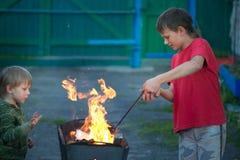 Barnlek med brand i gallret Royaltyfria Bilder