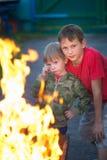 Barnlek med brand i gallret Arkivbild