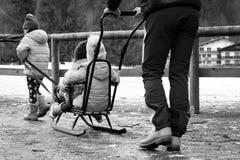 Barnlek med en släde i parkerar i vinter royaltyfria bilder