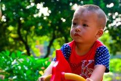 Barnlek med glad självhjälp går rundan royaltyfri foto