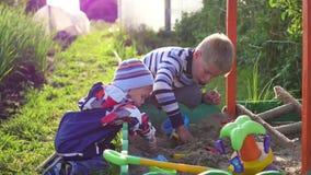 Barnlek med leksaker i sandlådan Underhållning och utomhus- lekar swallowtail för sommar för fjärilsdaggräs solig lager videofilmer