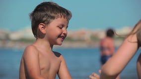 Barnlek med sand och vatten på stranden stock video