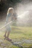Barnlek med strålar av vatten Arkivbild