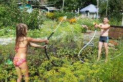 Barnlek med trädgårds- slangar Fotografering för Bildbyråer