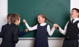Barnlek och hagyckel, pojkar drar de flätade trådarna för flickan, nära tom svart tavlabakgrund för skola, den iklädda klassikers Arkivbilder