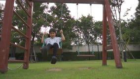 Barnlek på gunga i den lyckliga lekplatsen lager videofilmer