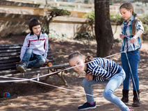 Barnlekar Flickan går till och med det tilltrasslade repet Arkivfoto