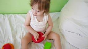 Barnlekar i rum på vit säng med röda och gröna kuber och cirklar Bildande leksaker för förträning och dagis arkivfilmer
